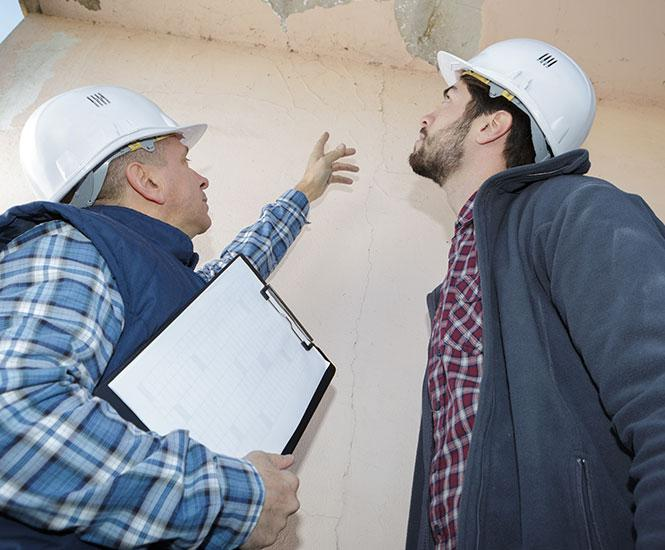 Mold Inspections in Atlanta, GA, with two inspectors looking at a damaged wall and ceiling with mold